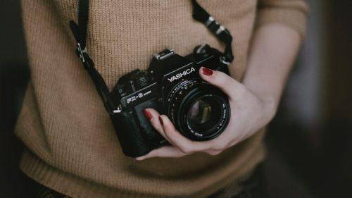 女性がカメラを片手で持っている