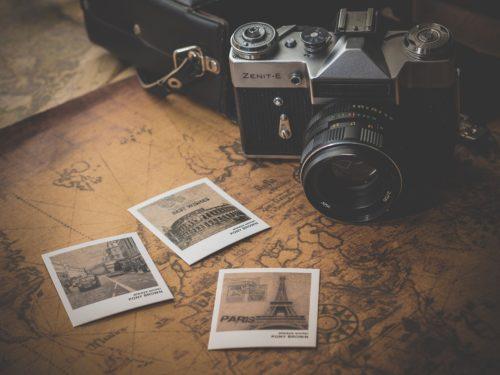 世界地図の上にカメラと3枚の写真