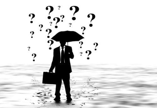 大雨の中で傘をさすサラリーマン