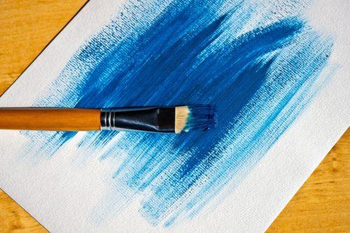 一本の筆と青く塗られた画用紙