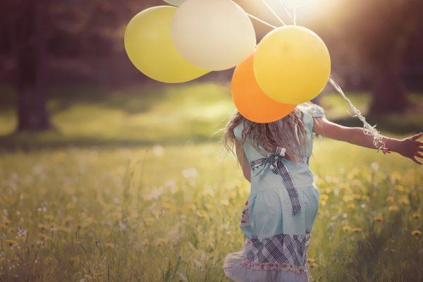 芝生の上でカラフルな風船を持つ少女
