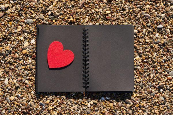 砂利道に黒いメモ帳と赤いハート