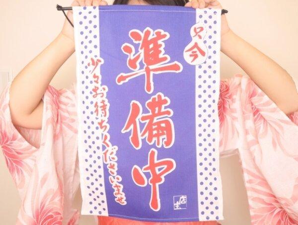 浴衣の女性が「準備中」の旗を持っている