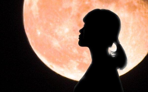暗闇の中の満月と女性
